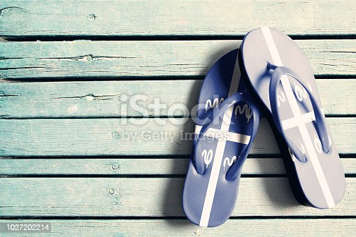 Flag of Martinique on flip-flops, with blue wooden boards in background. Summer time flat scene, with copy space. Horizontal orientation.