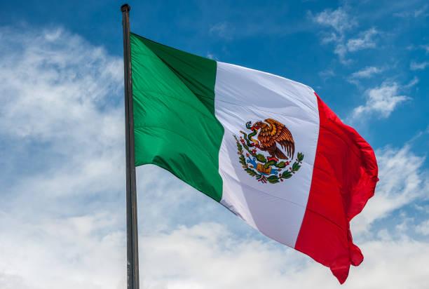 bandera de méxico sobre azul cielo nublado - bandera mexico fotografías e imágenes de stock