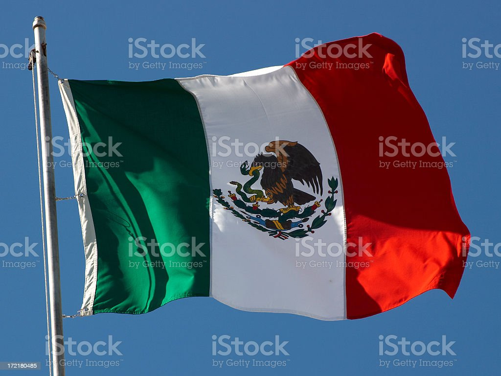 Flag of Mexico waving from the top of a flagpole royalty-free stock photo