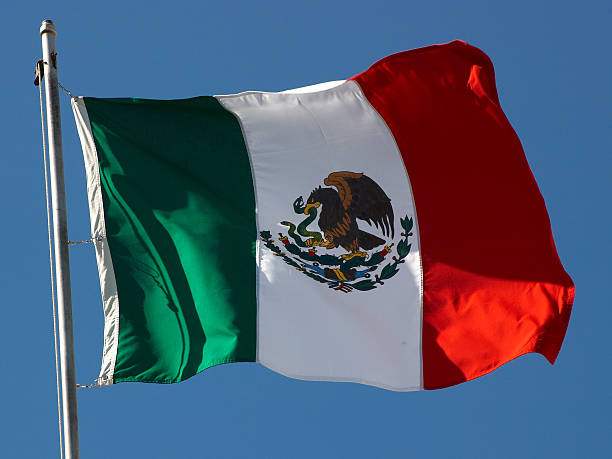 Flag of Mexico waving from the top of a flagpole stock photo