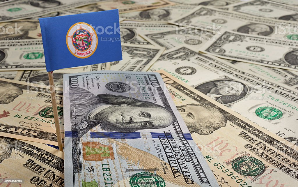 Flag of Minnesota sticking in various american banknotes.(series stock photo
