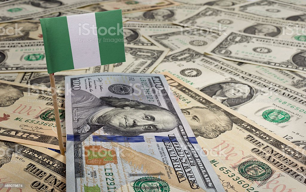 Flag of Nigeria sticking in various american banknotes.(series) stock photo