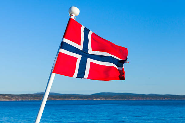 flag of norway over sea and blue sky - norwegen fahne stock-fotos und bilder