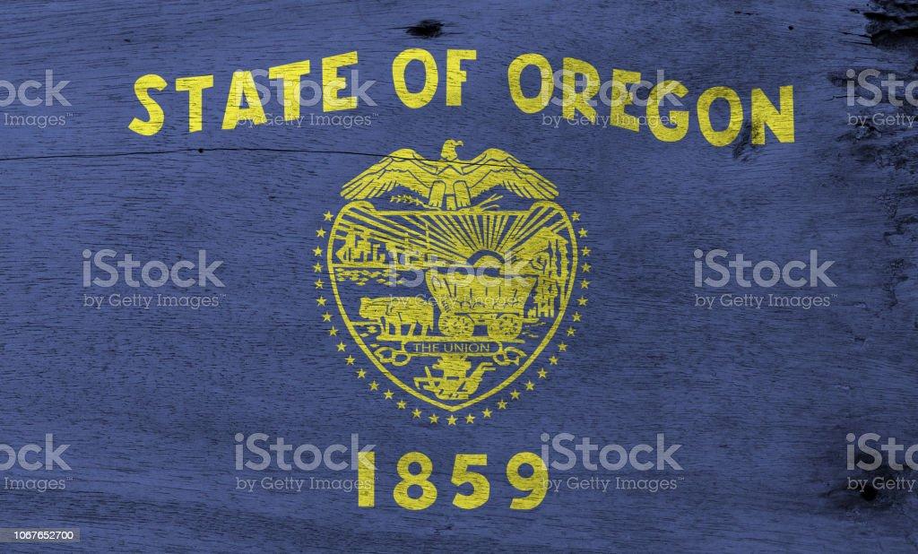 Flag of Oregon on wooden plate background. Grunge Oregon flag texture. stock photo