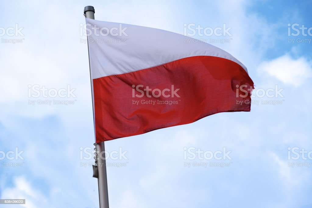 Flag of Poland with horizontal stripes in white and red, national symbol or sign of the european country, fluttering in the wind against the blue sky with clouds on a sunny day stock photo