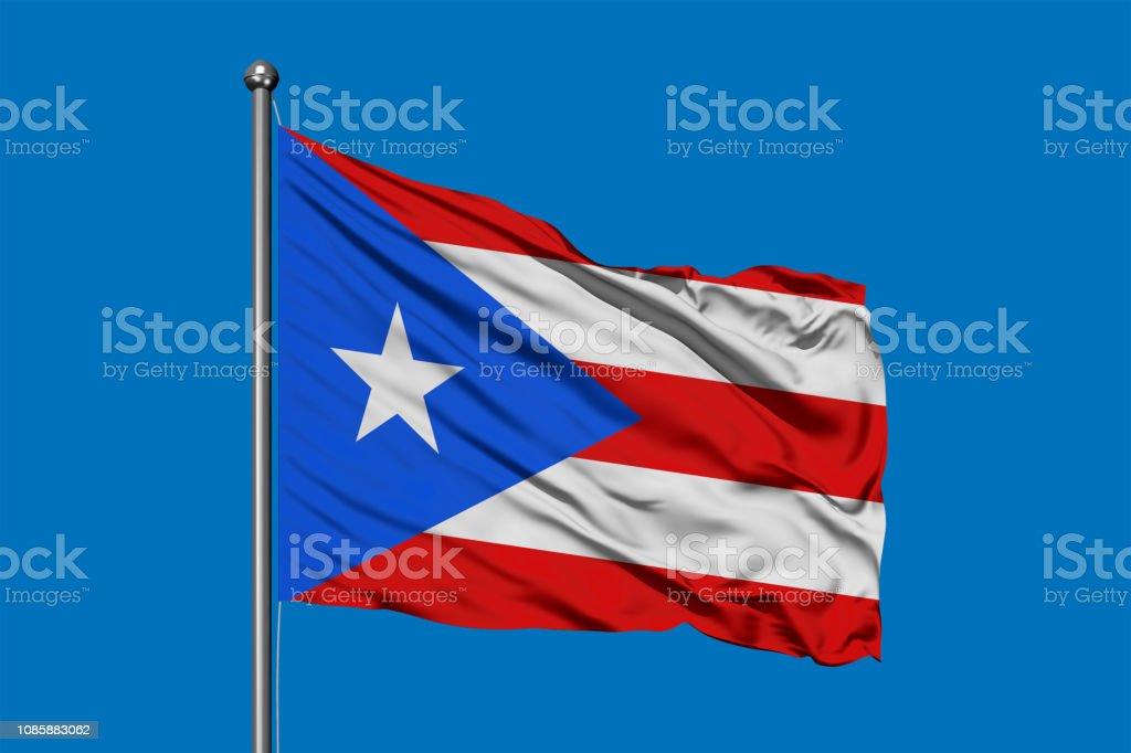 Bandera de Puerto Rico ondeando en el viento contra el cielo azul profundo. - foto de stock