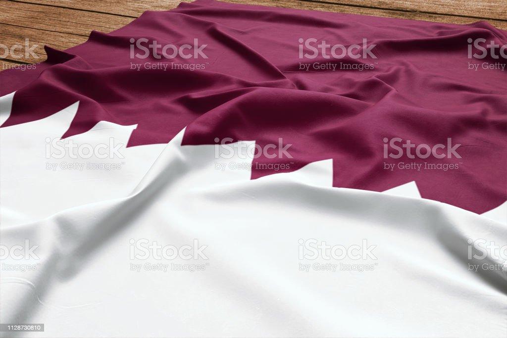 Bandera de Qatar sobre un fondo de escritorio de madera. Vista superior de seda bandera qatarí. - foto de stock