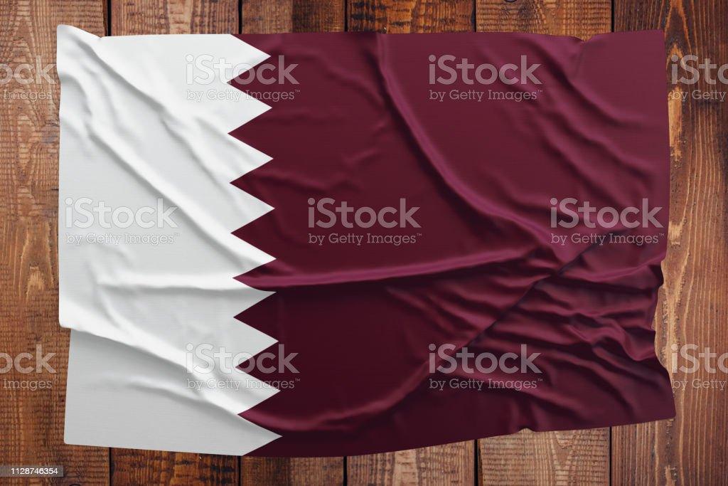 Bandera de Qatar sobre un fondo de mesa de madera. Vista superior arrugado bandera qatarí. - foto de stock