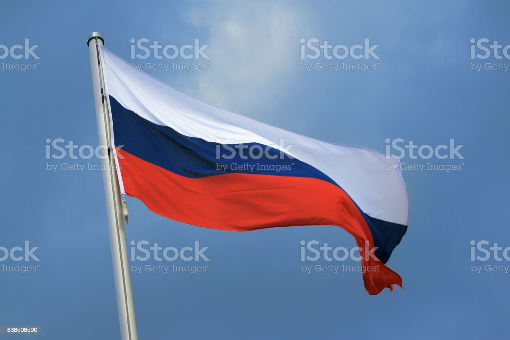 Flag of Russia with stripes in white, blue and red, national symbol or sign of the country, fluttering in the wind against the blue sky with clouds on a sunny day stock photo