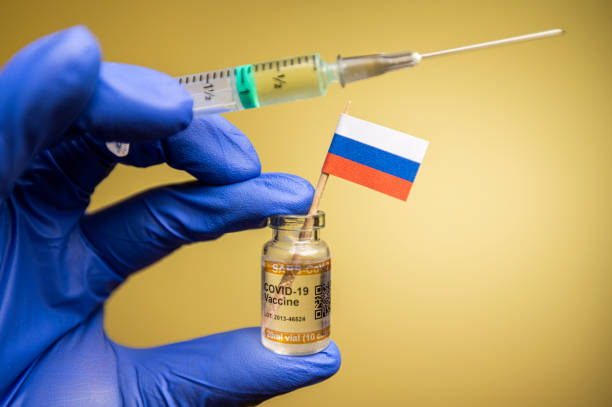 Flag of Russia with vaccine vial held by healthcare worker's hand in blue surgical protective glove. Concept of vaccine patriotism, nationalism and solidarity stock photo
