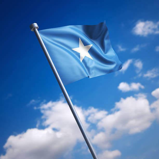 flag of somalia against blue sky - somalia stock photos and pictures