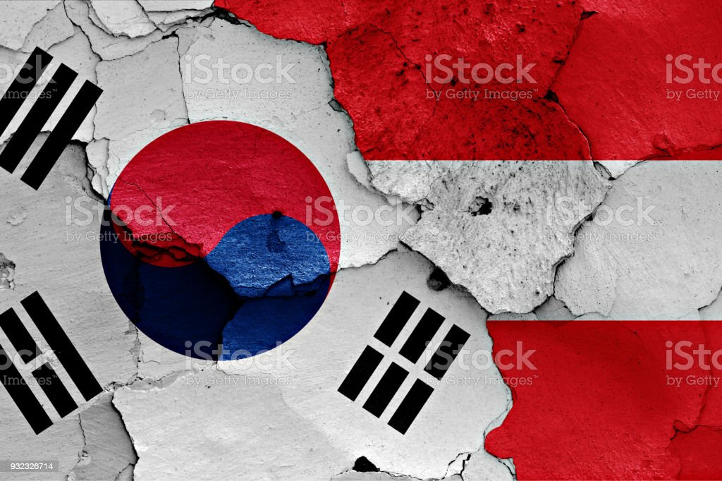 flag of South Korea and Austria painted on cracked wall stock photo