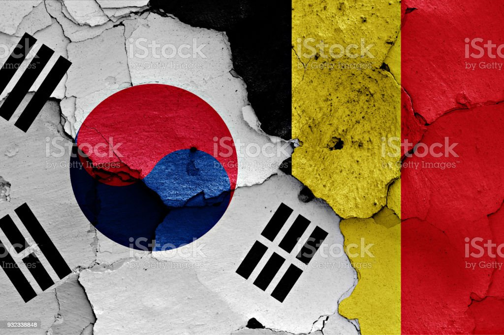 flag of South Korea and Belgium painted on cracked wall stock photo