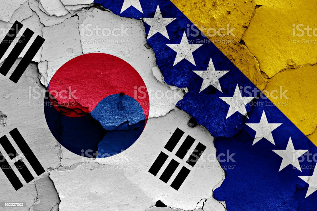 flag of South Korea and Bosnia and Herzegovina painted on cracked wall stock photo