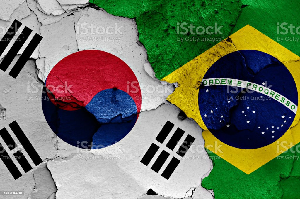 flag of South Korea and Brazil painted on cracked wall stock photo