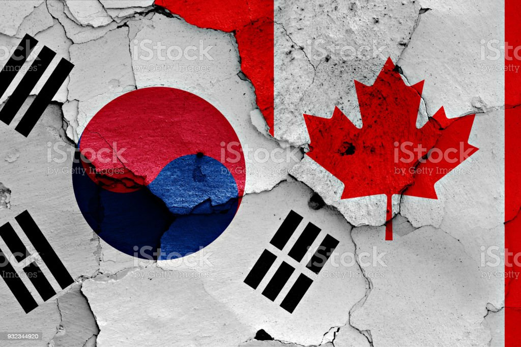 flag of South Korea and Canada painted on cracked wall stock photo