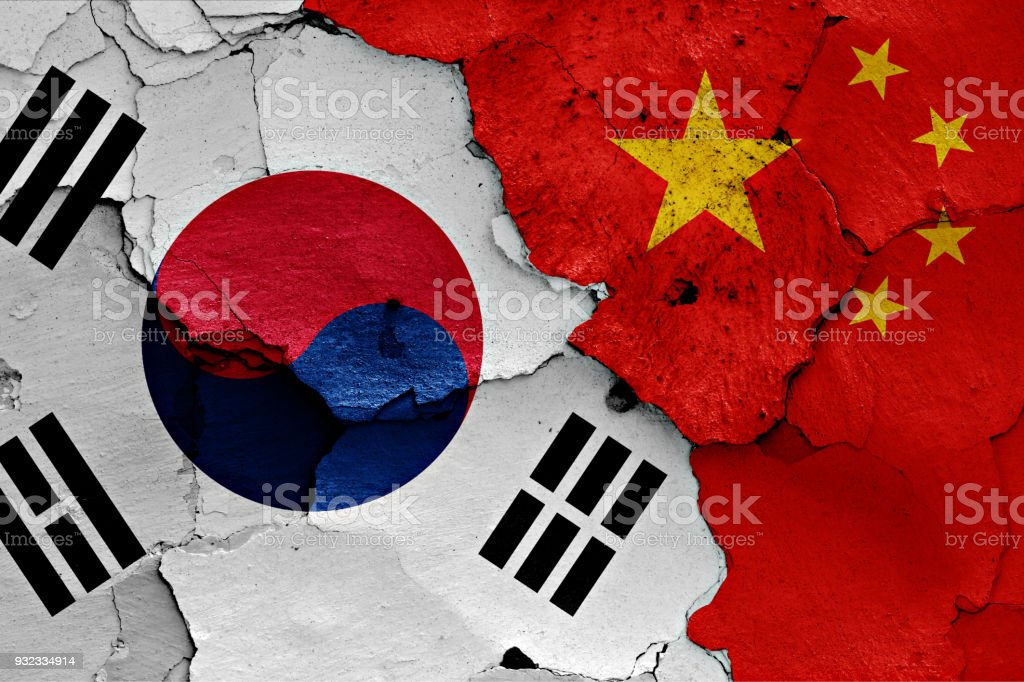 flag of South Korea and China painted on cracked wall stock photo