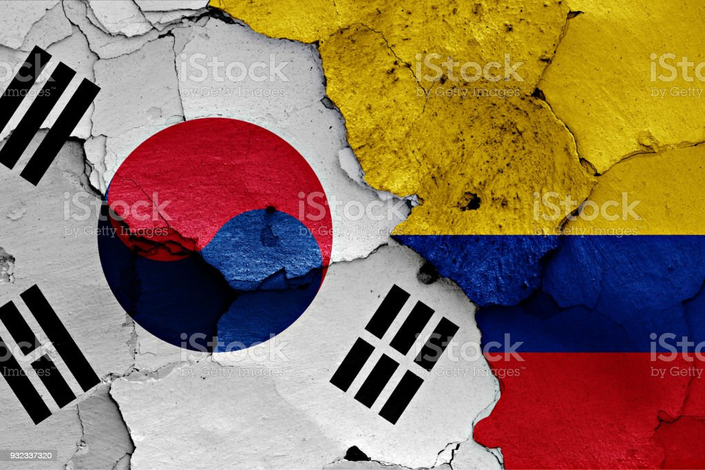 flag of South Korea and Colombia painted on cracked wall stock photo