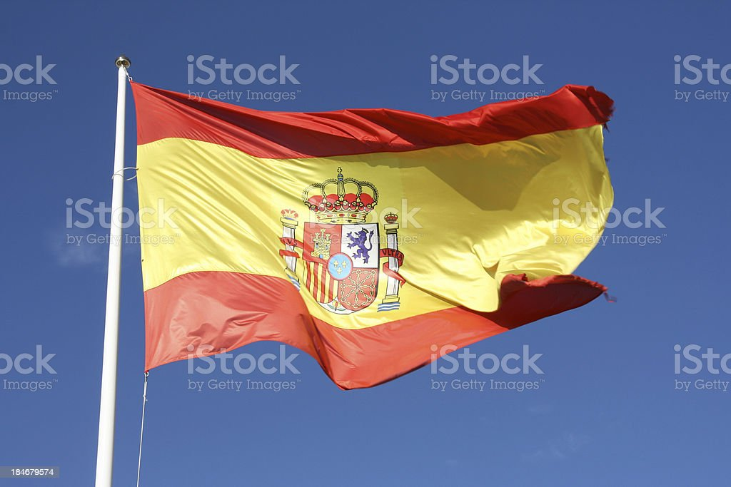 Flag of Spain waving in breeze with blue sky behind stock photo