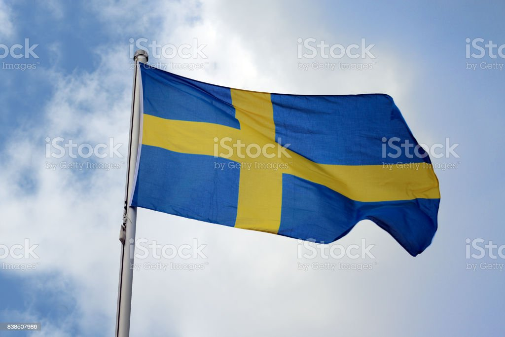 Flag of Sweden with a yellow cross on a blue background, national symbol or sign of the european country, fluttering in the wind against the blue sky with clouds on a sunny day stock photo