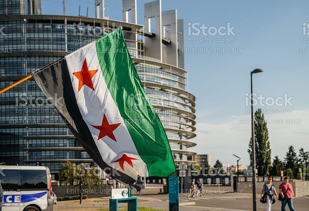 Bandera de siria con coche de policía y el edificio del Parlamento Europeo - foto de stock