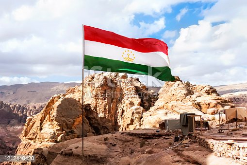 flag of Tajikistan is flying in the wind against a cloudy sky in the mountains.