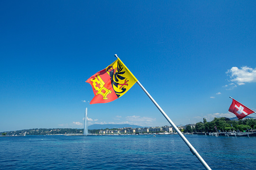 Flag of the Geneva Canton in the city center of Geneva, on the Leman lake. The iconic Jet d'Eau (Water Jet) can be seen in the background