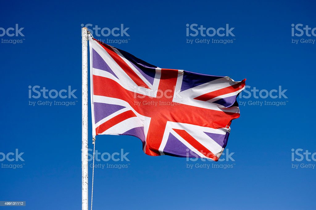 Flag of the United Kingdom waving in the wind stock photo