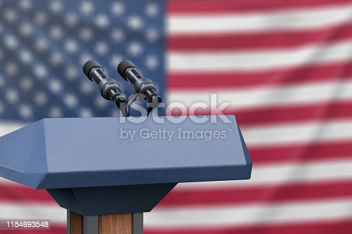 Podium lectern with two microphones and United States flag in background