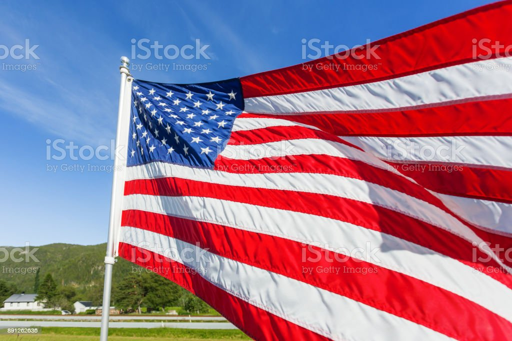 Flag of the United States of America (American flag or The Stars and Stripes, Old Glory, The Star-Spangled Banner) waving in the wind against summer forest landscape in sunny day. stock photo