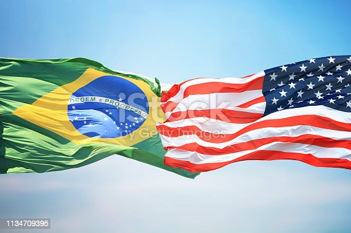 Flag of the USA and Brazil against the background of the blue sky
