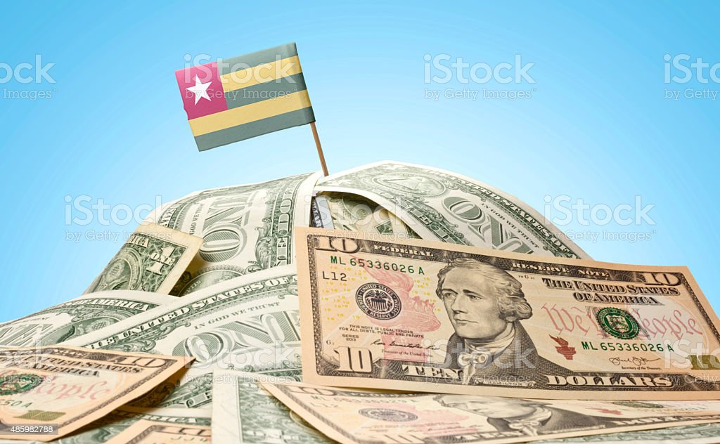 Flag of Togo sticking in american banknotes.(series) stock photo
