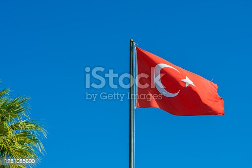 Flag of Turkey rise waving to the wind with sky in the background. Waving national flag of Turkey. Travel, tourism.
