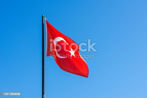 Flag of Turkey rise waving to the wind with sky in the background. Waving national flag of Turkey. Symbol of Turkish people.