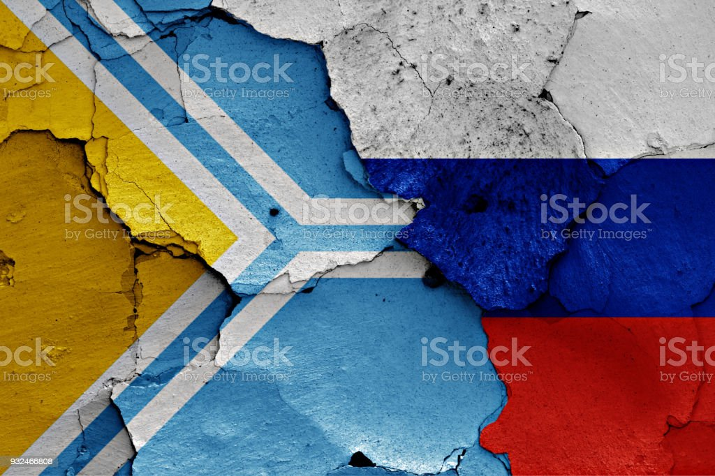 flag of Tuva and Russia painted on cracked wall stock photo