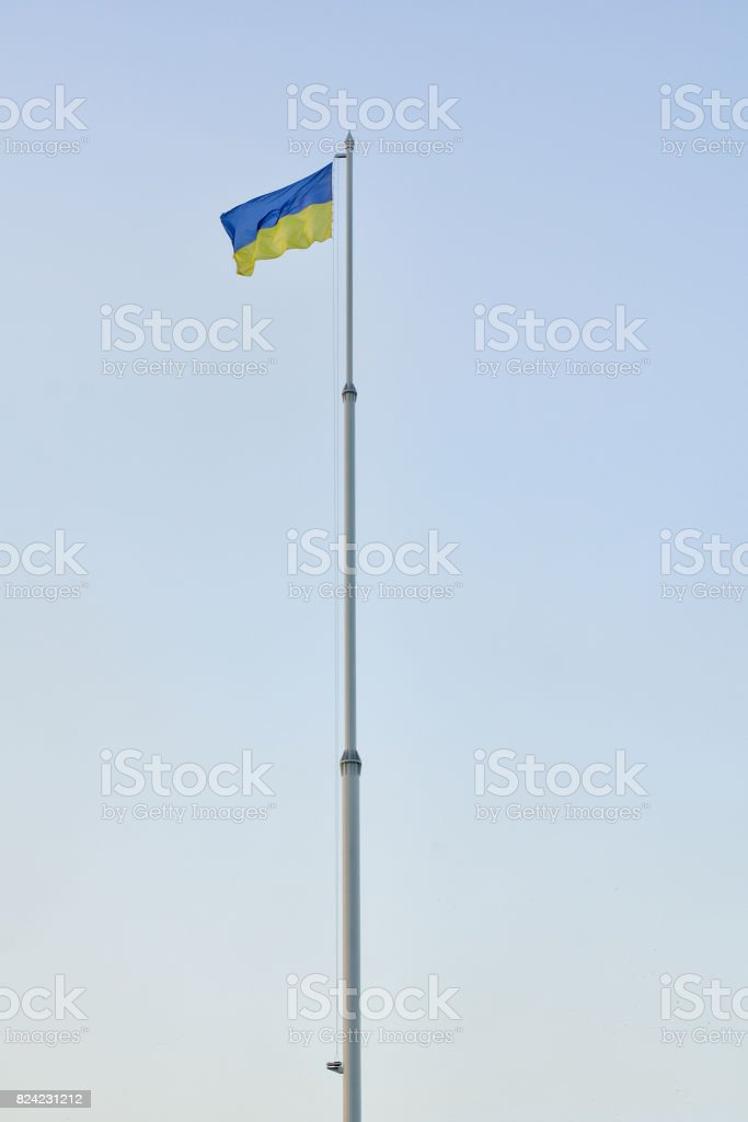 Flag of Ukraine on flagpole against the blue sky, vertical frame stock photo