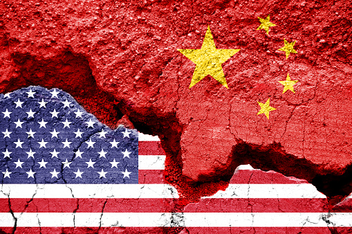 Flag of USA and China on a cracked background. Concept of crisis between two nations, Washington and Beijing