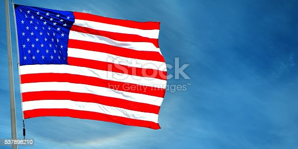537898300istockphoto Flag of USA waving against blue sky 537898210