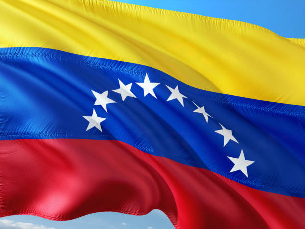 flag of venezuela waving in the wind against deep blue sky. high quality fabric. - venezuelan flag stock photos and pictures