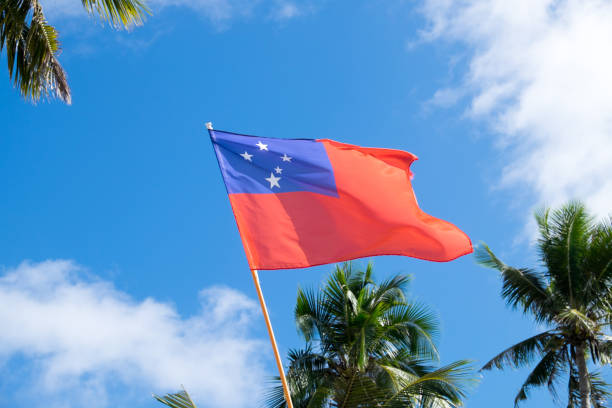 Flag of Western Samoa features the Southern Cross. Flying against a blue sky with clouds and palm trees stock photo