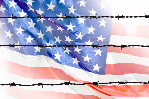 flag of wires Metal fence with barbed wire on a USA flag. Separation concept, borders protection.Social issues on refugees or illegal immigrants deportation stock pictures, royalty-free photos & images