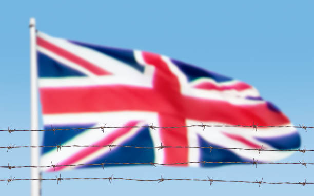 flag of wires Metal fence with barbed wire on a Britain flag. Separation concept, borders protection. Social issues on refugees or illegal immigrants deportation stock pictures, royalty-free photos & images