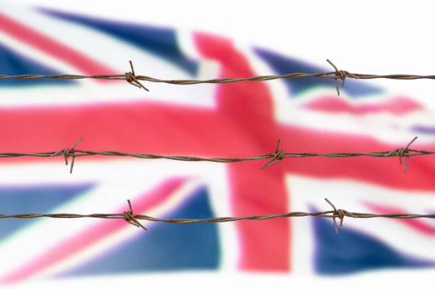 flag of wires Metal fence with barbed wire on a Britain flag. Separation concept, borders protection.Social issues on refugees or illegal immigrants deportation stock pictures, royalty-free photos & images
