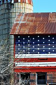 American flag painted on abandoned barn by silo.