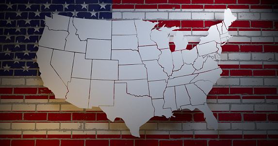 istock US flag on brick wall with map silhouette. 3D illustration 1128226921