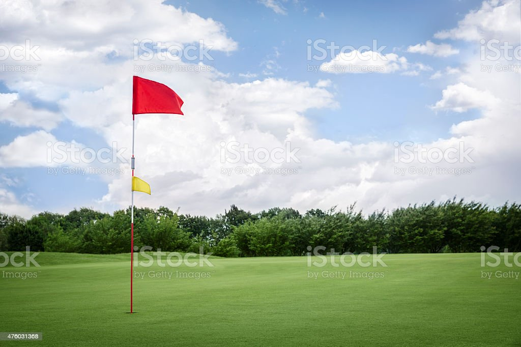 Flag on golf fairway with copyspace. stock photo