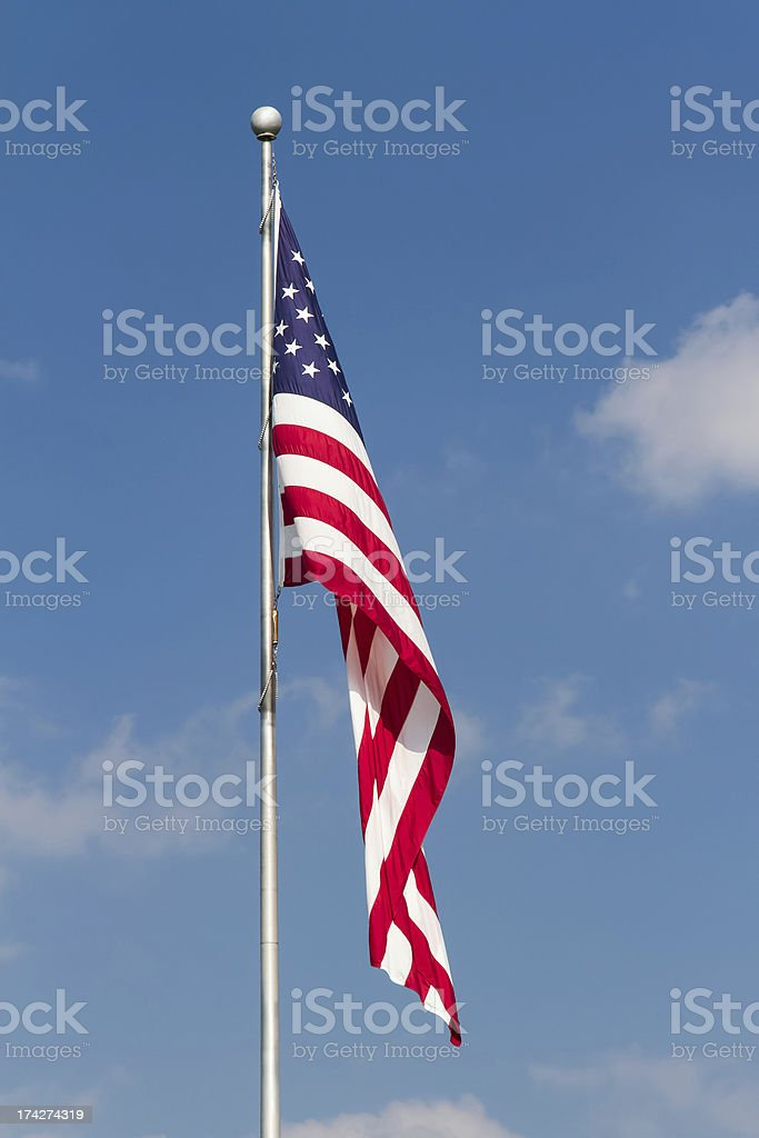 US Flag on Pole with Blue Sky stock photo