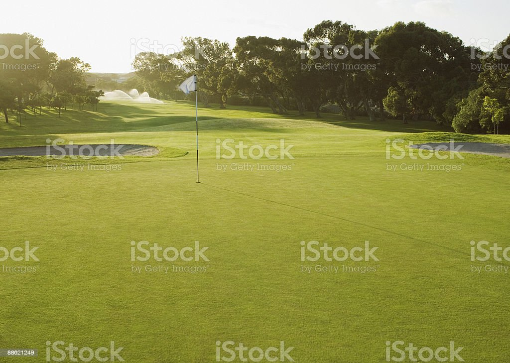 Flag on putting green of golf course stock photo