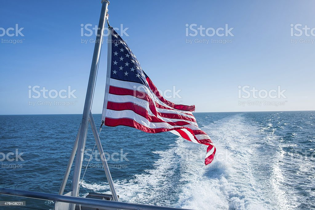 USA Flag on Stern of Boat with Wake stock photo
