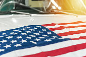 istock USA flag on the hood of a white car 643053452